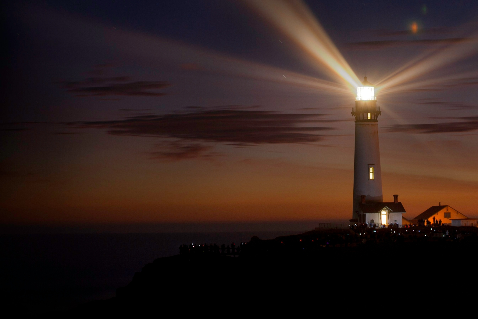 Photo of a lighthouse lit up at night. This photo represents the light of compassion shining through the night.